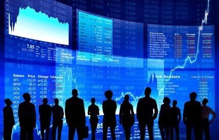 אנשים עומדים מול גרפים של פעילות כלכלית של המשק