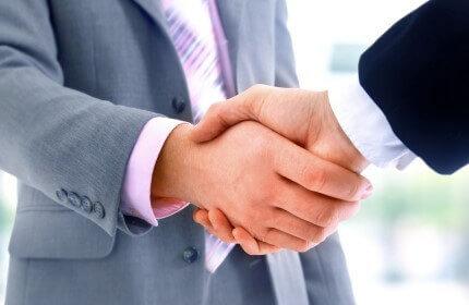 איש עסקים לוחץ יד לאחר סגירת עסקה להקמת עסק בזכיינות