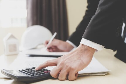 איש עסקים חותם על טפסים ומחשב במחשבון