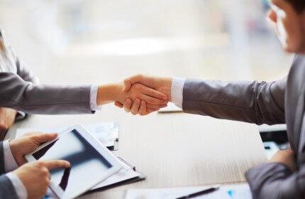 שני אנשי עסקים לוחצים ידיים בפגישה עסקית