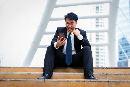 איש עסקים יושב על מדרגה ומתבונן בפלאפון