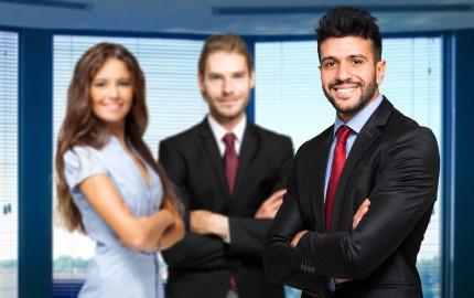 שלושה אנשי עסקים עומדים בשילוב ידיים